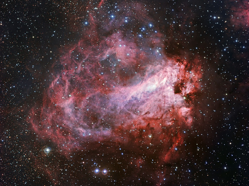 This image of the rose-coloured star forming region Messier 17 was captured by the Wide Field Imager on the MPG/ESO 2.2-metre telescope at ESO's La Silla Observatory in Chile. It is one of the sharpest images showing the entire nebula and not only reveals its full size but also retains fine detail throughout the cosmic landscape of gas clouds, dust and newborn stars.
