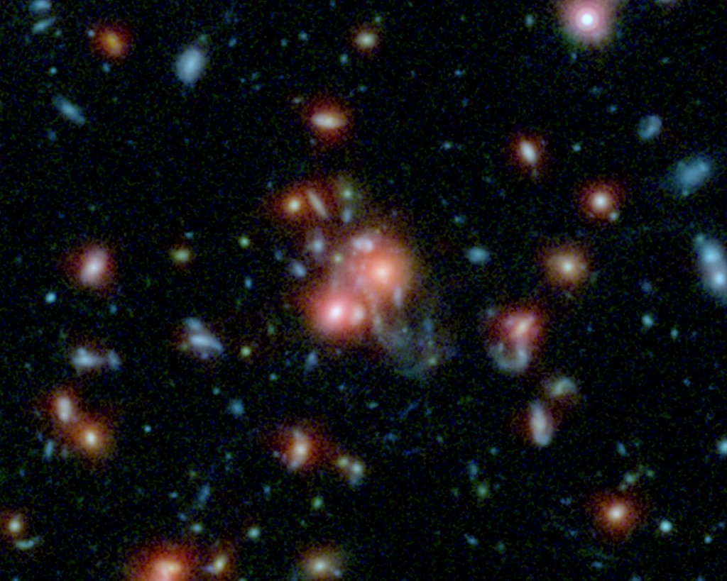 This image, using data from Spitzer and the Hubble Space Telescope, shows the galaxy cluster SpARCS1049.