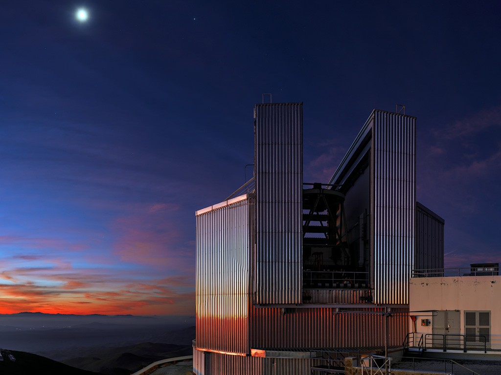 This striking picture of the New Technology Telescope (NTT) was taken just after sunset at ESO's La Silla Observatory, located in the Norte Chico in outskirts of the Chilean Atacama Desert. The Moon has already begun its journey across the evening sky, and is shining brightly overhead. The Sun dips below the horizon to the left of the frame, soaking the clouds in a rich orange colour. The warm glow of the last rays of sunshine are caught by the reflective surface of the NTT walls. The purpose of this metallic dome is to stop the telescope's enclosure from heating up during the day. This would affect the telescope's observations, as rising warm air and turbulence blur images and worsen the astronomical seeing. It is not just the telescope's enclosure that is designed to reduce heat accumulation during the day; the concrete platforms and parking spaces around the site are all painted white to increase the amount of light reflected from their surface.
