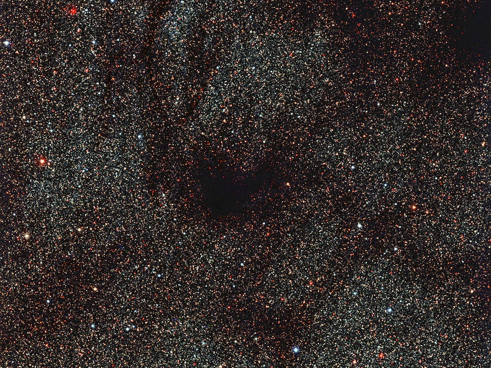 Rather than showing spectacular objects, some of the most surprising images of the Universe instead focus on emptiness. This new image from the 2.2-metre MPG/ESO telescope shows dark tentacles swirling outwards from a dark, blank spot of space in the centre of the frame, particularly conspicuous against the dense peppering of bright gold and red stars across the rest of the image. This region is not a hole in the cosmos, or an empty patch of sky. The dark lanes are actually made up of thick, opaque dust lying between us and the packed star field behind it. This obscuring dust forms part of a dark molecular cloud, cold and dense areas where large quantities of dust and molecular gas mingle and block the visible light emitted by more distant stars. It is still unclear how these clouds form, but they are thought to be the very early stages of new star formation — in the future, the subject of this image may well collapse inwards on itself to form a new star system. Although the cloud in this image is a fairly anonymous resident of the nearby Universe — catalogued as LDN1774 — one of the most famous examples of a molecular cloud is the very similar Barnard 68, which lies some 500 light-years away from us. Barnard 68 has been observed extensively using ESO telescopes, both in visible (eso9924a) and infrared light (eso9934, eso0102a). As shown in these different images, it is possible to probe through dark cosmic dust using infrared light, but visible-light observations such as those shown in this VLT image cannot see beyond the smokescreen. This image was taken by the Wide Field Imager, an instrument mounted on ESO's 2.2-metre MPG/ESO telescope at La Silla, Chile.
