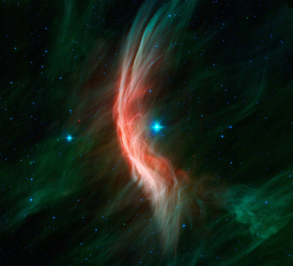 "The giant star Zeta Ophiuchi is having a ""shocking"" effect on the surrounding dust clouds in this infrared image from NASAs Spitzer Space Telescope. Stellar winds flowing out from this fast-moving star are making ripples in the dust as it approaches, creating a bow shock seen as glowing gossamer threads, which, for this star, are only seen in infrared light. Zeta Ophiuchi is a young, large and hot star located around 370 light-years away. It dwarfs our own sun in many ways -- it is about six times hotter, eight times wider, 20 times more massive, and about 80,000 times as bright. Even at its great distance, it would be one of the brightest stars in the sky were it not largely obscured by foreground dust clouds. This massive star is travelling at a snappy pace of about 54,000 mph (24 kilometers per second), fast enough to break the sound barrier in the surrounding interstellar material. Because of this motion, it creates a spectacular bow shock ahead of its direction of travel (to the left). The structure is analogous to the ripples that precede the bow of a ship as it moves through the water, or the sonic boom of an airplane hitting supersonic speeds. The fine filaments of dust surrounding the star glow primarily at shorter infrared wavelengths, rendered here in green. The area of the shock pops out dramatically at longer infrared wavelengths, creating the red highlights. A bright bow shock like this would normally be seen in visible light as well, but because it is hidden behind a curtain of dust, only the longer infrared wavelengths of light seen by Spitzer can reach us. Bow shocks are commonly seen when two different regions of gas and dust slam into one another. Zeta Ophiuchi, like other massive stars, generates a strong wind of hot gas particles flowing out from its surface. This expanding wind collides with the tenuous clouds of interstellar gas and dust about half a light-year away from the star, which is almost 800 times the distance from the sun to Pluto. The speed of the winds added to the stars supersonic motion result in the spectacular collision seen here.  Our own sun has significantly weaker solar winds and is passing much more slowly through our galactic neighborhood so it may not have a bow shock at all. NASAs twin Voyager spacecraft are headed away from the solar system and are currently about three times farther out than Pluto. They will likely pass beyond the influence of the sun into interstellar space in the next few years, though this is a much gentler transition than that seen around Zeta Ophiuchi. For this Spitzer image, infrared light at wavelengths of 3.6 and 4.5 microns is rendered in blue, 8.0 microns in green, and 24 microns in red."
