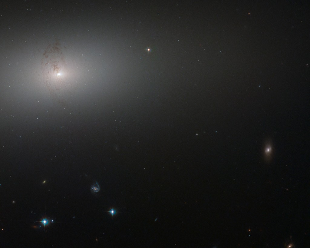 Like a lighthouse in the fog the luminous core of NGC 2768 slowly fades outwards to a dull white haze in this image taken by the NASA/ESA Hubble Space Telescope. NGC 2768 is an elliptical galaxy in the constellation of Ursa Major (The Great Bear). It is a huge bundle of stars, dominated by a bright central region, where a supermassive black hole feasts on a constant stream of gas and dust being fed to it by its galactic host. The galaxy is also marked by a prominent plume of dust reaching out from the centre and lying perpendicular to the galaxy's plane. This dust conceals a symmetrical, s-shaped pair of jets that are being produced by the supermassive black hole as it feeds.