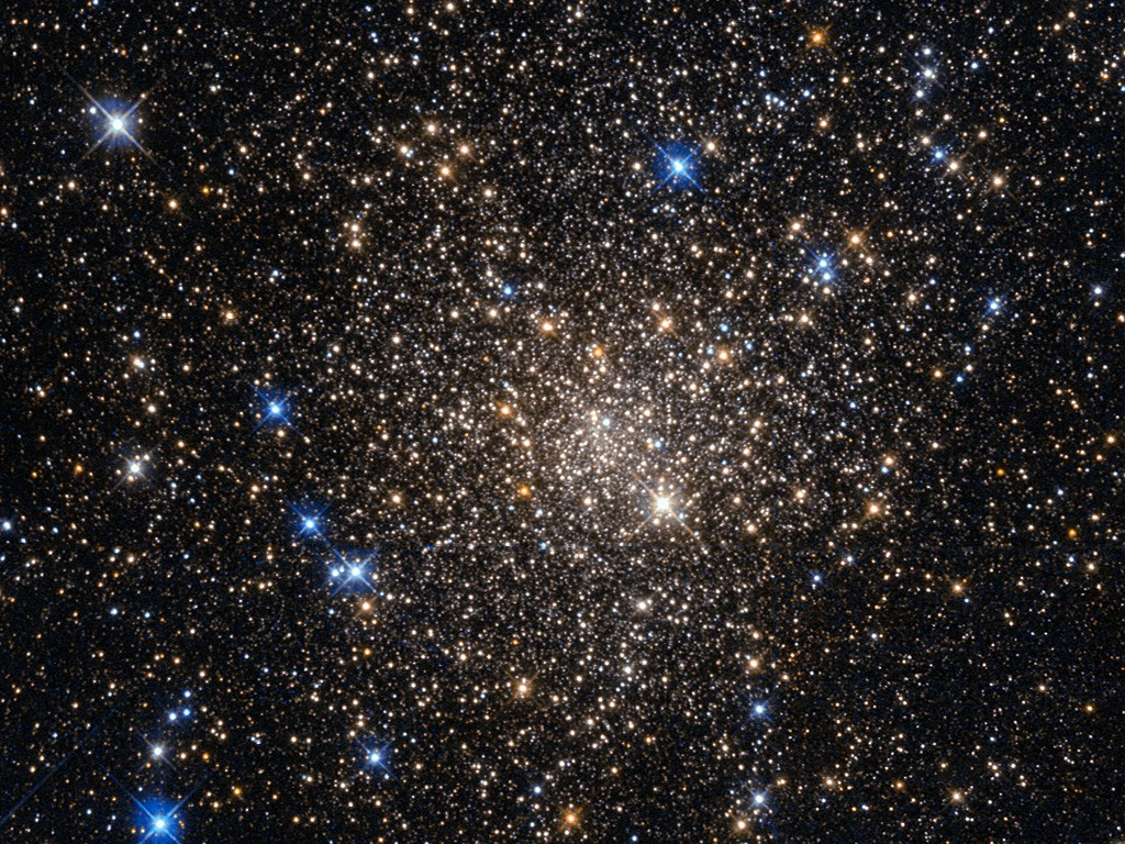 This image, taken with the Wide Field Planetary Camera 2 on board the NASA/ESA Hubble Space Telescope, shows the globular cluster Terzan 1. Lying around 20 000 light-years from us in the constellation of Scorpius (The Scorpion), it is one of about 150 globular clusters belonging to our galaxy, the Milky Way. Typical globular clusters are collections of around a hundred thousand stars, held together by their mutual gravitational attraction in a spherical shape a few hundred light-years across. It is thought that every galaxy has a population of globular clusters. Some, like the Milky Way, have a few hundred, while giant elliptical galaxies can have several thousand. They contain some of the oldest stars in a galaxy, hence the reddish colours of the stars in this image — the bright blue ones are foreground stars, not part of the cluster. The ages of the stars in the globular cluster tell us that they were formed during the early stages of galaxy formation! Studying them can also help us to understand how galaxies formed. Terzan 1, like many globular clusters, is a source of X-rays. It is likely that these X-rays come from binary star systems that contain a dense neutron star and a normal star. The neutron star drags material from the companion star, causing a burst of X-ray emission. The system then enters a quiescent phase in which the neutron star cools, giving off X-ray emission with different characteristics, before enough material from the companion builds up to trigger another outburst.