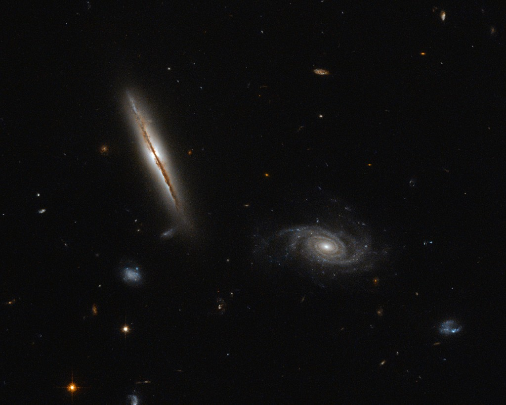 Despite its unassuming appearance, the edge-on spiral galaxy captured in the left half of this NASA/ESA Hubble Space Telescope image is actually quite remarkable. Located about one billion light-years away in the constellation of Eridanus, this striking galaxy — known as LO95 0313-192 — has a spiral shape similar to that of the Milky Way. It has a large central bulge, and arms speckled with brightly glowing gas mottled by thick lanes of dark dust. Its companion, sitting pretty in the right of the frame, is known rather unpoetically as [LOY2001] J031549.8-190623. Jets, outbursts of superheated gas moving at close to the speed of light, have long been associated with the cores of giant elliptical galaxies, and galaxies in the process of merging. However, in an unexpected discovery, astronomers found LO95 0313-192 to have intense radio jets spewing out from its centre! The galaxy appears to have two more regions that are also strongly emitting in the radio part of the spectrum, making it even rarer still. The discovery of these giant jets in 2003 — not visible in this image, but indicated in this earlier Hubble composite — has been followed by the unearthing of a further three spiral galaxies containing radio-emitting jets in recent years. This growing class of unusual spirals continues to raise significant questions about how jets are produced within galaxies, and how they are thrown out into the cosmos.