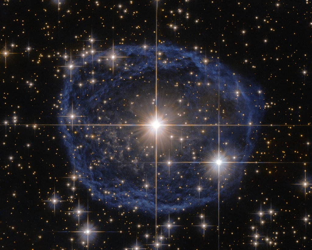 Sparkling at the centre of this beautiful NASA/ESA Hubble Space Telescope image is a Wolf–Rayet star known as WR 31a, located about 30 000 light-years away in the constellation of Carina (The Keel). The distinctive blue bubble appearing to encircle WR 31a, and its uncatalogued stellar sidekick, is a Wolf–Rayet nebula — an interstellar cloud of dust, hydrogen, helium and other gases. Created when speedy stellar winds interact with the outer layers of hydrogen ejected by Wolf–Rayet stars, these nebulae are frequently ring-shaped or spherical. The bubble — estimated to have formed around 20 000 years ago — is expanding at a rate of around 220 000 kilometres per hour! Unfortunately, the lifecycle of a Wolf–Rayet star is only a few hundred thousand years — the blink of an eye in cosmic terms. Despite beginning life with a mass at least 20 times that of the Sun, Wolf–Rayet stars typically lose half their mass in less than 100 000 years. And WR 31a is no exception to this case. It will, therefore, eventually end its life as a spectacular supernova, and the stellar material expelled from its explosion will later nourish a new generation of stars and planets.