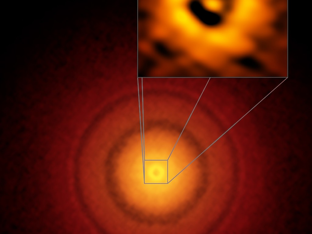 ALMA image of the planet-forming disc around the young, Sun-like star TW Hydrae. The inset image (upper right) zooms in on the gap nearest to the star, which is at the same distance as the Earth is from the Sun, suggesting an infant version of our home planet could be emerging from the dust and gas. The additional concentric light and dark features represent other planet-forming regions farther out in the disc.