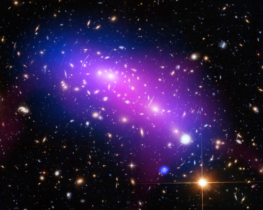 At first glance, this cosmic kaleidoscope of purple, blue and pink offers a strikingly beautiful — and serene — snapshot of the cosmos. However, this multi-coloured haze actually marks the site of two colliding galaxy clusters, forming a single object known as MACS J0416.1-2403 (or MACS J0416 for short). MACS J0416 is located about 4.3 billion light-years from Earth, in the constellation of Eridanus. This new image of the cluster combines data from three different telescopes: the NASA/ESA Hubble Space Telescope (showing the galaxies and stars), the NASA Chandra X-ray Observatory (diffuse emission in blue), and the NRAO Jansky Very Large Array (diffuse emission in pink). Each telescope shows a different element of the cluster, allowing astronomers to study MACS J0416 in detail. As with all galaxy clusters, MACS J0416 contains a significant amount of dark matter, which leaves a detectable imprint in visible light by distorting the images of background galaxies. In this image, this dark matter appears to align well with the blue-hued hot gas, suggesting that the two clusters have not yet collided; if the clusters had already smashed into one another, the dark matter and gas would have separated. MACS J0416 also contains other features — such as a compact core of hot gas — that would likely have been disrupted had a collision already occurred. Together with five other galaxy clusters, MACS J0416 is playing a leading role in the Hubble Frontier Fields programme, for which this data was obtained. Owing to its huge mass, the cluster is in fact bending the light of background objects, acting as a magnifying lens. Astronomers can use this phenomenon to find galaxies that existed only hundreds of million years after the big bang. For more information on both Frontier Fields and the phenomenon of gravitational lensing, see Hubblecast 90: The final frontier. Links  Hubblecast 90: The final      frontier Link to Hubblesite release