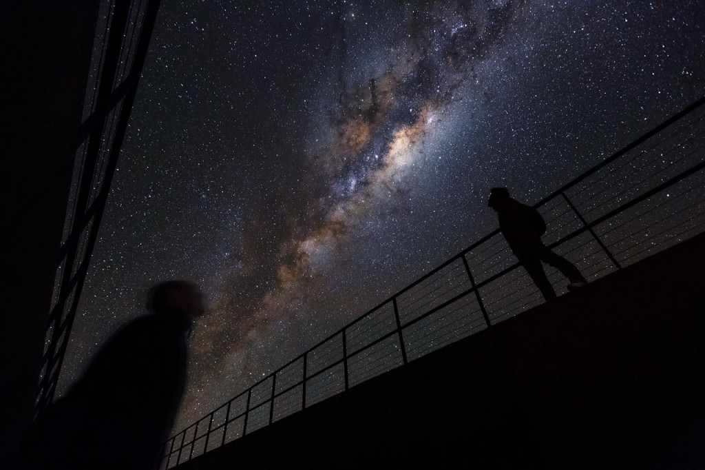Deep in the Chilean Desert, astronomers staying at ESO's La Residencia, the VLT Observatory's hotel, witness a skyscape like few others on Earth.  Designed by the German architects Auer+Weber+Assoziierte, La Residencia provides an oasis for those working at ESO's Paranal Observatory. The Atacama Desert is one of the harshest landscapes imaginable. Extreme dryness, intense ultraviolet radiation from the Sun, and high altitude are a normal part of everyday life. However, come nightfall, La Residencia experiences some of the best observing conditions in the world.  La Residencia and ESO's Very Large Telescope (VLT) — housed at the Paranal Observatory — are far from sources of light pollution, and experience exceptionally clear atmospheric conditions. On moonless nights, the sky can be so clear and dark that light from the Milky Way casts a shadow on the ground! These factors permit high quality scientific observations to be made as well as offering amazing conditions for astrophotography, exemplified in this stunning shot taken by Luis Calçada, a motion graphic designer at ESO's headquarters in Garching, Germany. In this photograph, the plane of the Milky Way can be seen above La Residencia, as passing staff members take a moment to admire the spectacular sight.