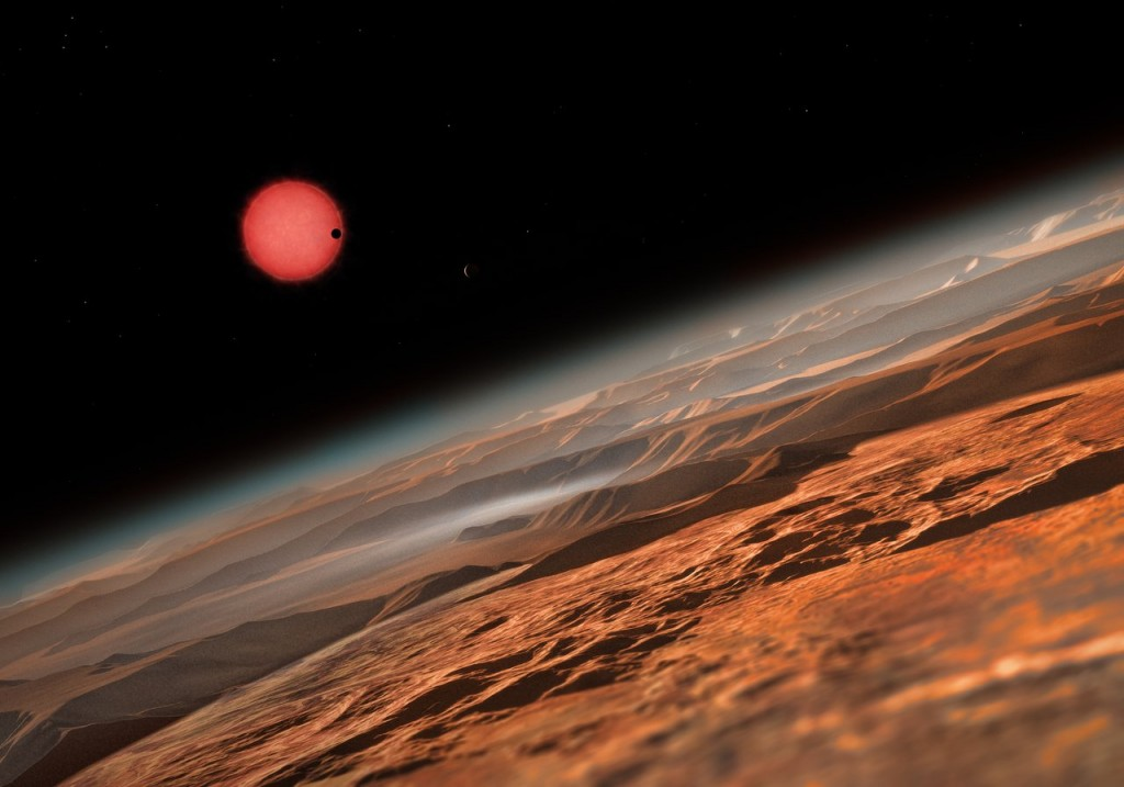 This artist's impression shows an imagined view from close to one of the three planets orbiting an ultracool dwarf star just 40 light-years from Earth that were discovered using the TRAPPIST telescope at ESO's La Silla Observatory. These worlds have sizes and temperatures similar to those of Venus and Earth and are the best targets found so far for the search for life outside the Solar System. They are the first planets ever discovered around such a tiny and dim star. In this view one of the inner planets is seen in transit across the disc of its tiny and dim parent star.