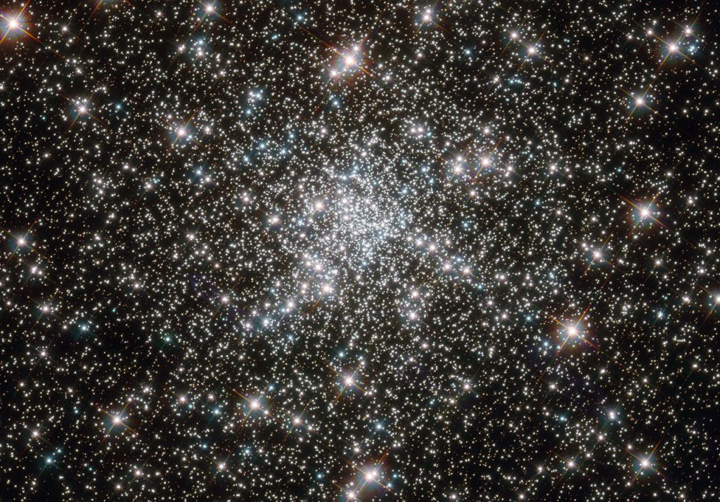 "Looking like a hoard of gems fit for an emperor's collection, this deep sky object called NGC 6752 is in fact far more worthy of admiration. It is a globular cluster, and at over 10 billion years old is one the most ancient collections of stars known. It has been blazing for well over twice as long long as our Solar System has existed. NGC 6752 contains a high number of ""blue straggler"" stars, some of which are visible in this image. These stars display characteristics of stars younger than their neighbours, despite models suggesting that most of the stars within globular clusters should have formed at approximately the same time. Their origin is therefore something of a mystery. Studies of NGC 6752 may shed light on this situation. It appears that a very high number — up to 38% — of the stars within its core region are binary systems. Collisions between stars in this turbulent area could produce the blue stragglers that are so prevalent. Lying 13 000 light-years distant, NGC 6752 is far beyond our reach, yet the clarity of Hubble's images brings it tantalisingly close."