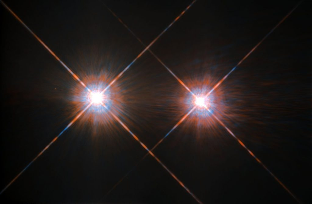 The closest star system to the Earth is the famous Alpha Centauri group. Located in the constellation of Centaurus (The Centaur), at a distance of 4.3 light-years, this system is made up of the binary formed by the stars Alpha Centauri A and Alpha Centauri B, plus the faint red dwarf Alpha Centauri C, also known as Proxima Centauri. The NASA/ESA Hubble Space Telescope has given us this stunning view of the bright Alpha Centauri A (on the left) and Alpha Centauri B (on the right), flashing like huge cosmic headlamps in the dark. The image was captured by the Wide Field and Planetary Camera 2 (WFPC2). WFPC2 was Hubble's most used instrument for the first 13 years of the space telescope's life, being replaced in 2009 by WFC3 during Servicing Mission 4. This portrait of Alpha Centauri was produced by observations carried out at optical and near-infrared wavelengths. Compared to the Sun, Alpha Centauri A is of the same stellar type G2, and slightly bigger, while Alpha Centauri B, a K1-type star, is slightly smaller. They orbit a common centre of gravity once every 80 years, with a minimum distance of about 11 times the distance between the Earth and the Sun. Because these two stars are, together with their sibling Proxima Centauri, the closest to Earth, they are among the best studied by astronomers. And they are also among the prime targets in the hunt for habitable exoplanets. Using the HARPS instrument astronomers already discovered a planet orbiting Alpha Centauri B. In August 2016 astronomers announced the discovery of an Earth-like planet in the habitable zone orbiting the star Proxima Centauri. Links:  Pale Red Dot Campaign  ESO press release on Proxima Centauri
