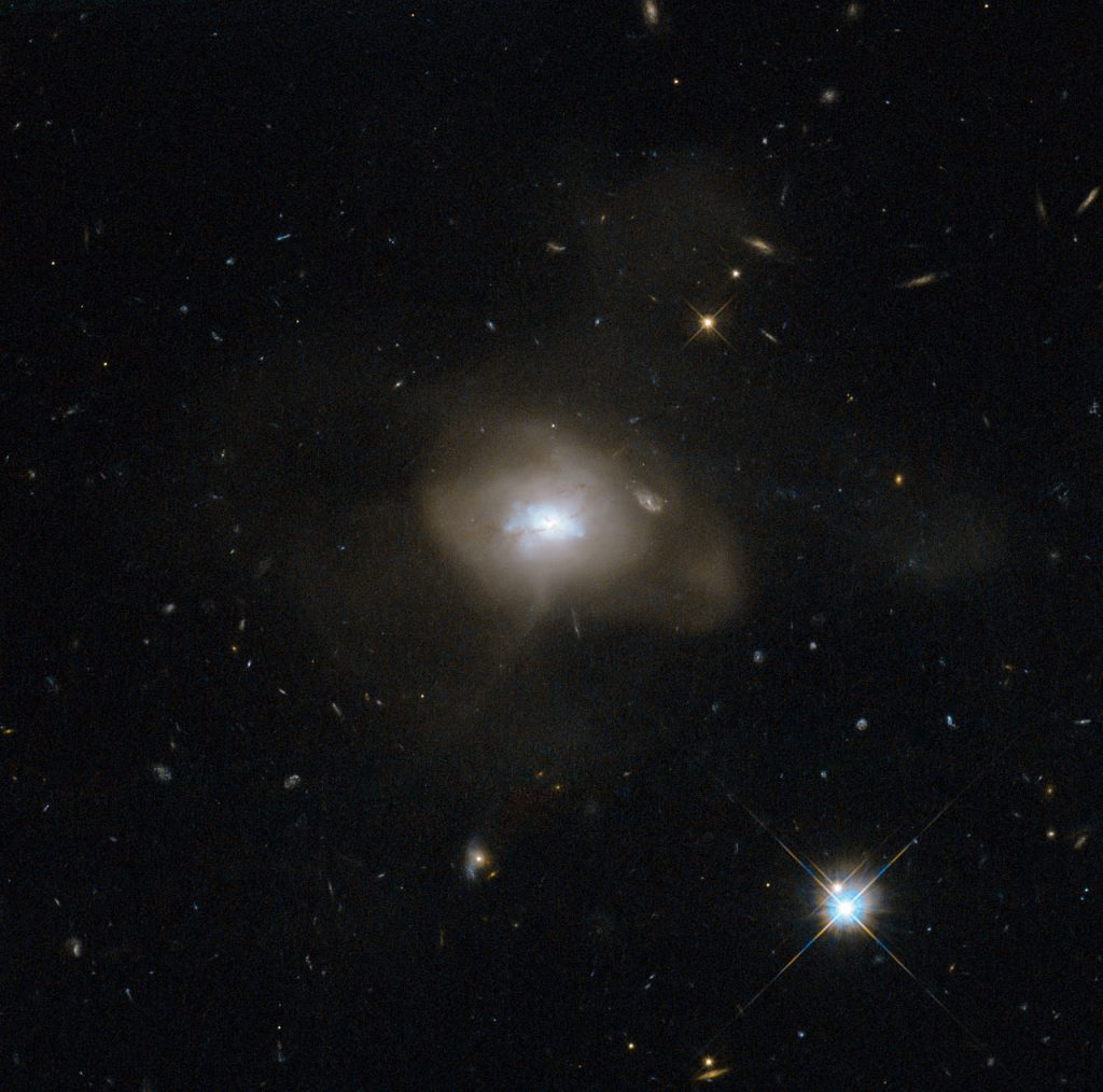 The NASA/ESA Hubble Space Telescope has caught sight of a soft, diffuse-looking galaxy that is probably the aftermath of a long-ago galactic collision. Two spiral galaxies, each perhaps much like the Milky Way, swirled together for millions of years. In such mergers, the original galaxies are often stretched and pulled apart as they wrap around a common centre of gravity. After a few back-and-forths, this starry tempest settles down into a new, round object. The now subdued celestial body, catalogued as SDSS J162702.56+432833.9, is technically known as an elliptical galaxy. When galaxies collide — a common event in the Universe — a fresh burst of star formation typically takes place as gas clouds mash together. At this point, the galaxy has a blue hue, but the colour does not mean it is cold: it is a result of the intense heat of newly formed blue–white stars. Those stars do not last long, and after a few billion years the reddish hues of aging smaller stars dominate an elliptical galaxy's spectrum. Hubble has helped astronomers learn of this sequence by observing galaxy mergers at all stages of the process. In SDSS J162702.56+432833.9, some ribbons of dust notably obscure parts of the conglomerated galaxy's central, bluish region. Those dust lanes could be remnants of the spiral arms of the recently departed galaxies. This picture was snapped by the Wide Field Camera of Hubble's Advanced Camera for Surveys. The image was made through a red (F625W) and a blue (F438W) filter. The field of view is approximately 2.4 by 2.4 arcminutes.