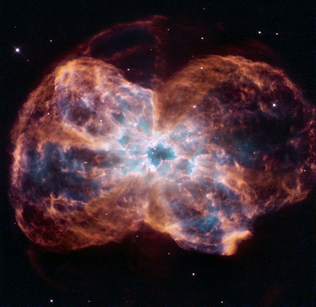 "This image of NGC 2440 shows the colourful ""last hurrah"" of a star like our Sun. The star is ending its life by casting off its outer layers of gas, which formed a cocoon around the star's remaining core. Ultraviolet light from the dying star makes the material glow. The burned-out star, called a white dwarf, is the white dot in the centre."