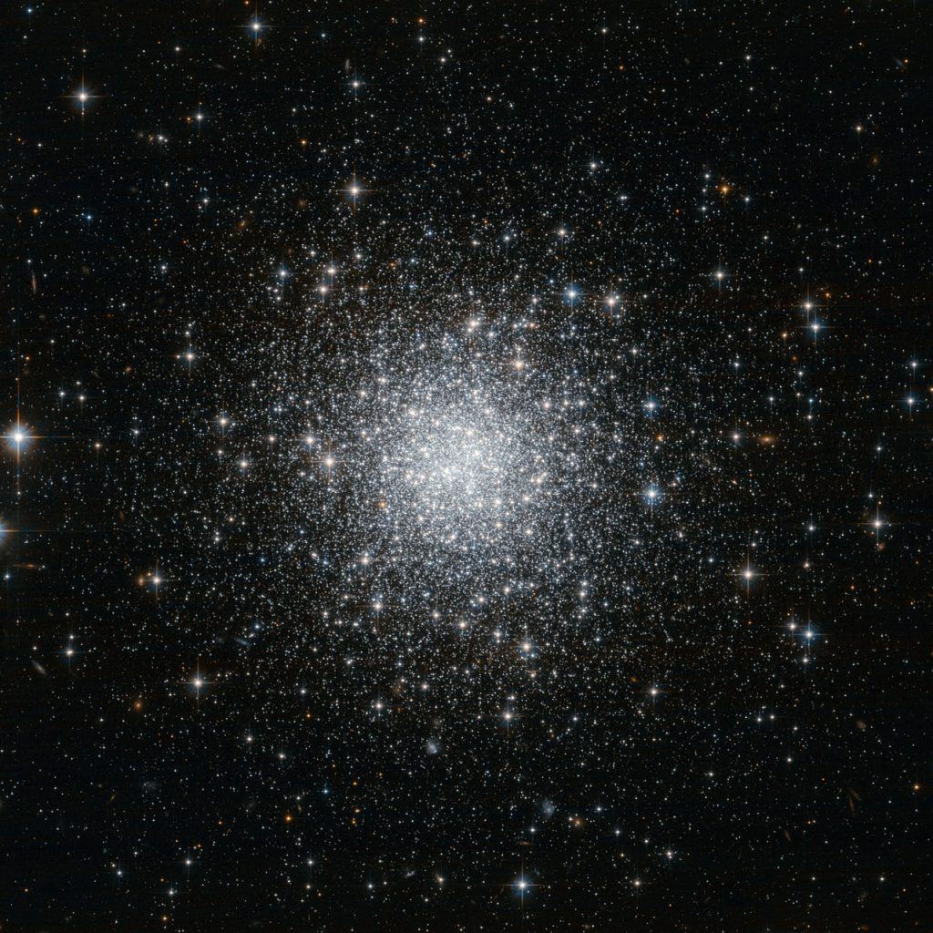 This NASA/ESA Hubble Space Telescope image shows a compact and distant globular star cluster that lies in one of the smallest constellations in the night sky, Delphinus (The Dolphin). Due to its modest size, great distance and relatively low brightness, NGC 7006 is often ignored by amateur astronomers. But even remote globular clusters such as this one appear bright and clear when imaged by Hubble's Advanced Camera for Surveys. NGC 7006 resides in the outskirts of the Milky Way. It is about 135 000 light-years away, five times the distance between the Sun and the centre of the galaxy, and it is part of the galactic halo. This roughly spherical region of the Milky Way is made up of dark matter, gas and sparsely distributed stellar clusters. Like other remote globular clusters, NGC 7006 provides important clues that help astronomers to understand how stars formed and assembled in the halo. The cluster now pictured by Hubble has a very eccentric orbit indicating that it may have formed independently, in a small galaxy outside our own that was then captured by the Milky Way. Although NGC 7006 is very distant for a Milky Way globular cluster, it is much closer than the many faint galaxies that can be seen in the background of this image. Each of these faint smudges is probably accompanied by many globular clusters similar to NGC 7006 that are too faint to be seen even by Hubble. This image was taken using the Wide Field Channel of the Advanced Camera for Surveys, in a combination of visible and near-infrared light. The field of view is a little over 3 by 3 arcminutes.
