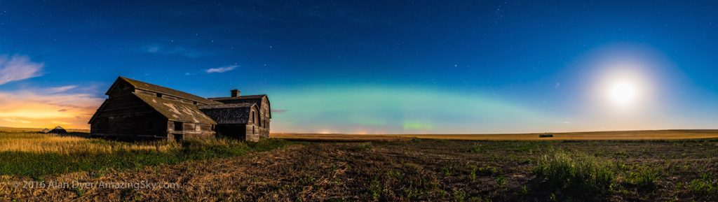 A diffuse arc of aurora and the rising waning gibbous Moon light the sky over the old barn near home at harvest time, September 19, 2016. The glows from Strathmore and Calgary light the clouds to the west at far left. The Big Dipper shines over the barn, with Capella and the stars of Perseus at right. The Pleiades are rising to the left of the Moon.  This is a panorama of 5 segments, with the 20mm lens and Nikon D750. Stitched with ACR.