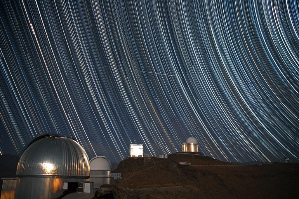 Here we see a swirling starscape above ESO's La Silla Observatory. A long series of individual images have been combined to form this striking shot, allowing the motion of the Earth to be captured as it rotates, with stars producing long trails around the sky's south pole as it does so. The familiar silver dome of the MPG/ESO 2.2-metre telescope is seen in the foreground. Moving into the shot, we next see the white dome of the ESO 1-metre Schmidt telescope, the rectangular building of the New Technology Telescope, and at the back, the double domes of the ESO 3.6-metre telescope with its adjacent smaller sibling, the now-decommissioned Coudé Auxiliary Telescope. But what are those streaks in the sky? Is it a bird? Is it a plane? Well, yes, it is indeed a plane. In fact, if you look very closely, you can see not one, but three horizontal trails from three separate planes, moving from left to right in the sky. They are not rotating with the stars, so it is clearly something a little closer to home… In fact, La Silla lies near a fairly busy flight path, and those streaks in the sky are aircraft travelling from Calama to Santiago. This image was taken by ESO Photo Ambassador Alexandre Santerne. When not taking these beautiful images, Alexandre travels around the world (including Chile) to pursue his research on extrasolar planets. Links  MPG/ESO 2.2-metre telescope ESO 1-metre Schmidt telescope  New Technology Telescope ESO 3.6-metre telescope Coudé Auxiliary Telescope